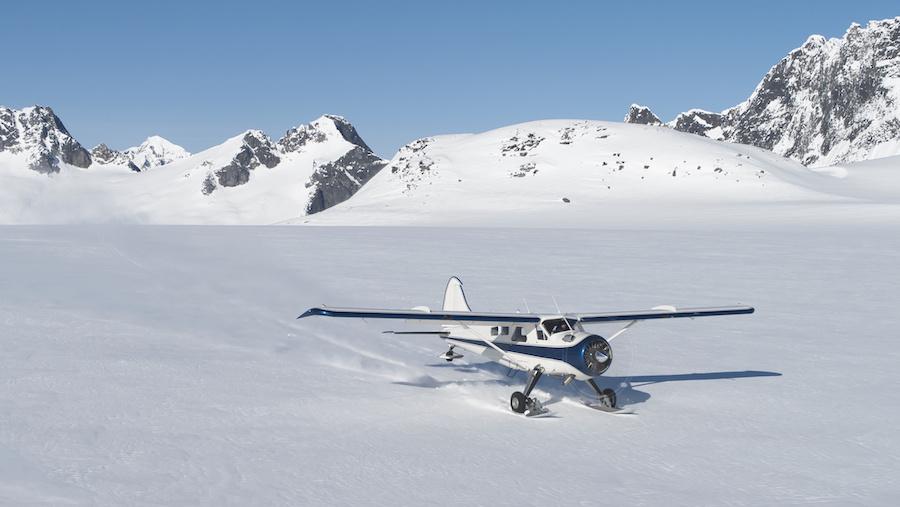 Small plane landing on snow in Alaskan mountains
